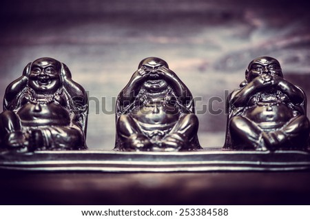 Three figures of Buddha philosophy on wooden background - stock photo