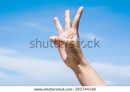 Three fingers on blue sky - stock photo