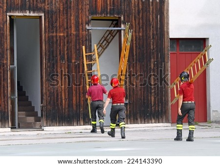 three firefighters during the fire drill mount a ladder - stock photo