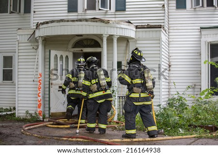 Three Firefighters on Fire Scene Walking into a building - stock photo