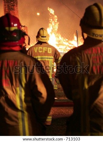 three fireman looking at fire burning - stock photo
