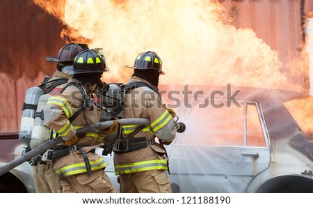 Three firemen extinguishing a car fire.