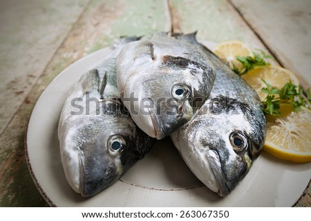 Three fishes (Sparus aurata) on a plate set on wooden table - stock photo