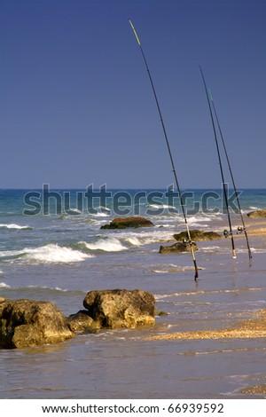 Three fishing rods on a rocky beach - stock photo