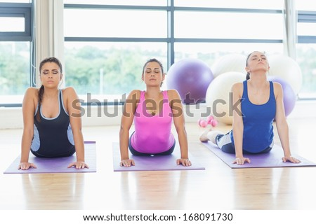 Three fit women doing the cobra pose in a bright fitness studio - stock photo