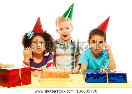 Three five years old kids, black and Caucasian, boys and girl with surprised and shocked expression and gesture on the birthday cake table - stock photo