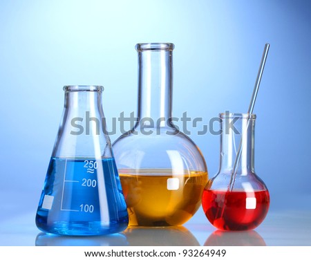Three flasks with color liquid with reflection on blue background