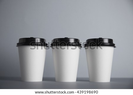 Three focused take away white paper cups with black caps presented in front, isolated on simple gray background - stock photo