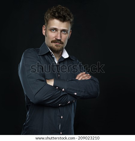 three fourths Portrait of serious confident man, office worker with crossed arms. Copy space right, dark background.  - stock photo