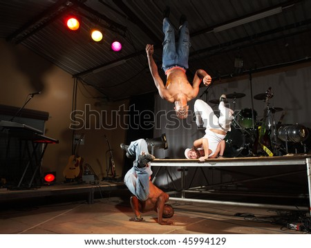 Three freestyle hip-hop dancers in a dancing practice session on stage with instruments. Lit with spotlights. Movement on edges of dancers - stock photo