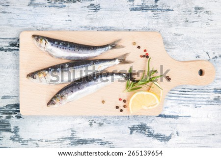 Three fresh anchovy fish on wooden kitchen board on white and blue wooden table, top view. Culinary seafood concept. Delicious healthy eating. - stock photo