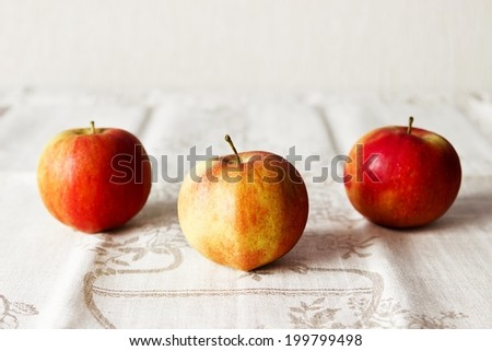 Three fresh apple fruit on textured linen background. Selective focus on foreground - stock photo
