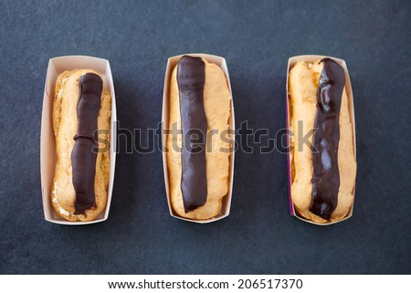 Three fresh cream chocolate eclairs in a row on a slate background
