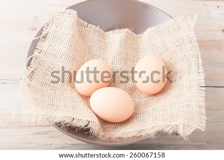 three fresh eggs in a bowl on wooden background