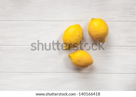 Three Fresh Lemons on a Whitewashed Wood Background - stock photo