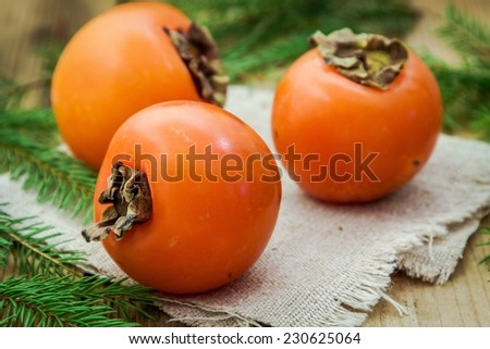 Three fresh organic persimmon on wooden background with pine tree - stock photo