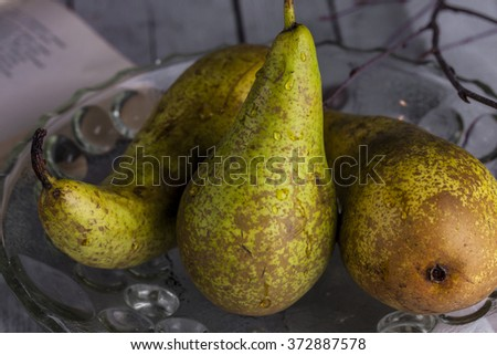 three fresh pears in a glass vase on a dark background