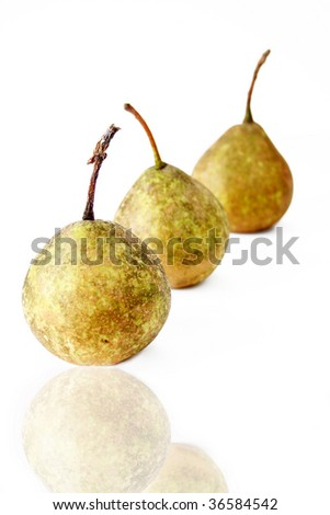 Three fresh pears on a white background with a reflection. Used a shallow depth of field and selective focus.