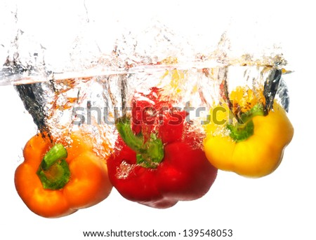 Three fresh peppers falling into water with a splash of water. Isolated on white background