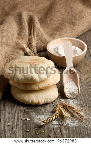 Three fresh pitas bread, ears of rye and bowl of flour on old wooden table