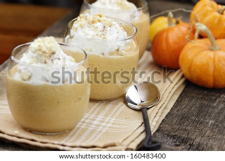 Three fresh Pumpkin Smoothies against a rustic background with shallow depth of field. Selective focus on center smoothie.  - stock photo