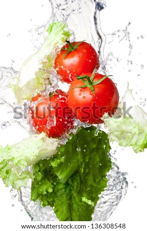 Three Fresh red Tomatoes and lettuce in splash water Isolated on a white background - stock photo
