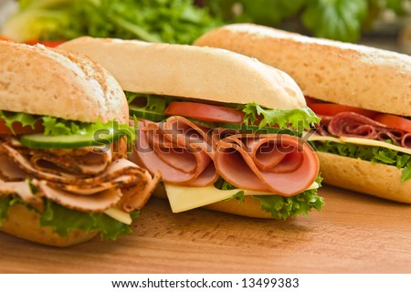 Three fresh sandwiches - turkey breast, ham & swiss and salami on a cutting board. Focus on the ham sandwich - stock photo