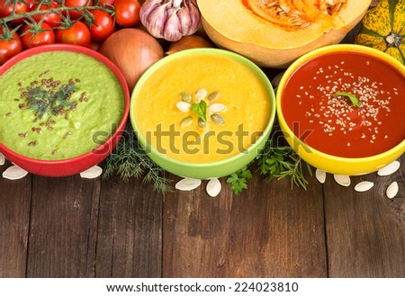 Three fresh soups in colorful bowls and vegetables on a wooden table - stock photo
