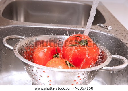 Three fresh tomatoes in colander splashing in water - stock photo
