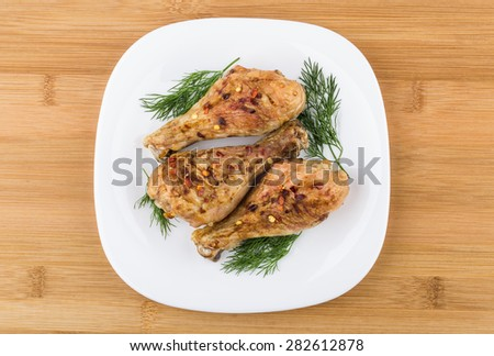 Three fried chicken legs sprinkled pepper with dill in glass plate on wooden board, top view - stock photo