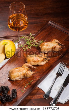 Three fried quails stuffed with prunes with white wine - stock photo