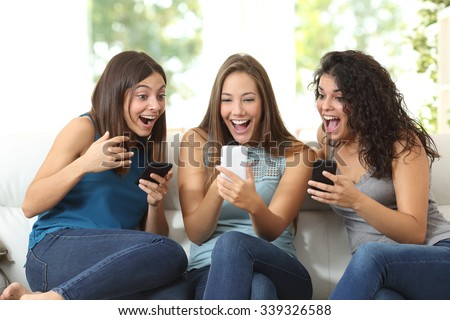Three friends amazed watching a smart phone sitting on a couch at home