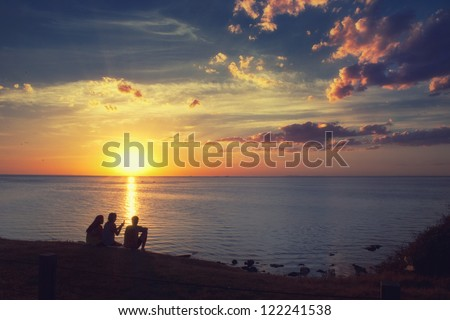 three friends are sitting and watching the sunset - stock photo