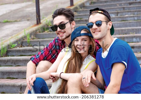 Three friends are watching and smiling at the camera. Young friends have fun together on the street and smile at each other. Funny guys make Selfie - stock photo