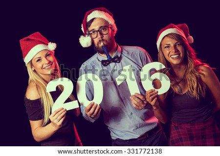 Three friends at a New Year's Party, enjoying and holding cardboard numbers 2016 - stock photo
