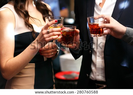 three friends drinking whiskey on  party in club