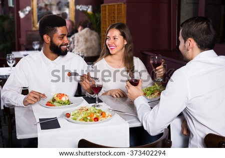 Three friends eating at restaurant table and chatting - stock photo