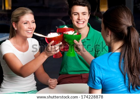Three friends enjoying ice cream in a restaurant. - stock photo