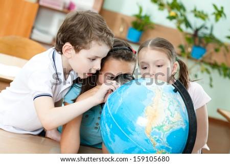 Three friends examine a school terrestrial globe - stock photo