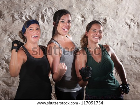 Three friends flexing their muscles in boot camp style workout - stock photo