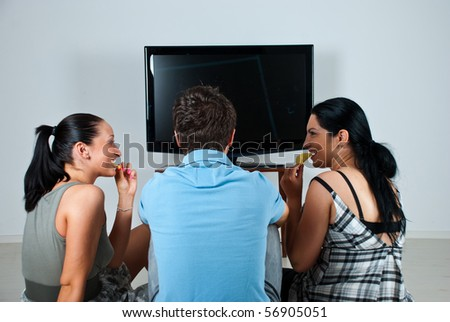 Three friends having a  funny conversation while watching soccer game at tv and eating chips