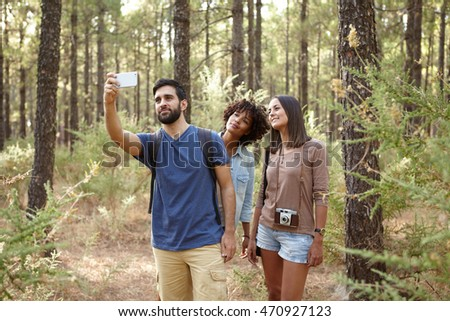 Three friends hiking through a pine tree forest in the late afternoon shadows and taking selfies in front of a tree
