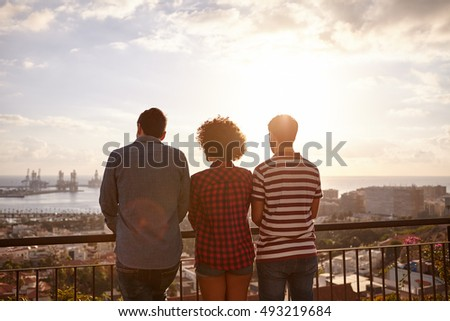 Three friends in casual clothing standing on a bridge looking out over a city while the sun is setting in front of them
