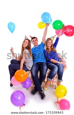 Three friends in hats with balloons sitting on the couch isolated