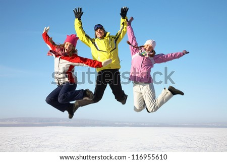 three friends joyfully jump into the sky over snow drifts in the winter - stock photo