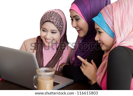 three friends laughing at content on a laptop at cafe