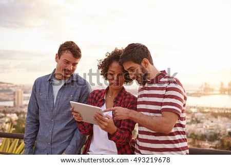 Three friends looking and pointing at a tablet looking at it with interest while wearing casual clothing