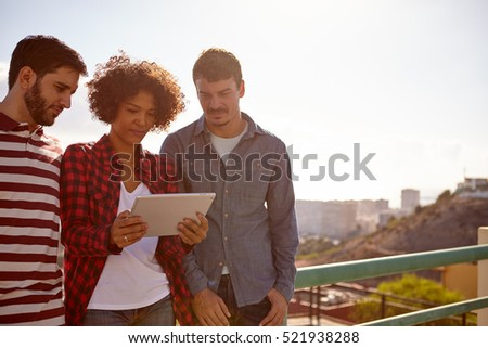 Three friends looking with great concentration at a tablet, the girl standing between the young men is holding