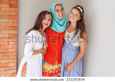 three friends of different religions standing happily together - stock photo