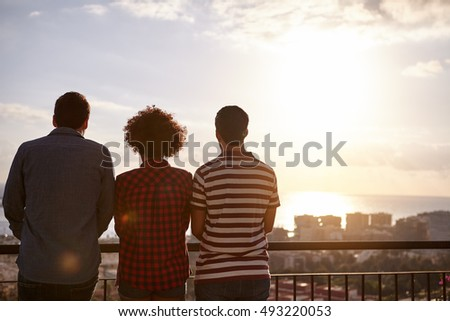 Three friends on a bridge looking out over the city at a sun setting while wearing casual clothing their hands in front of them
